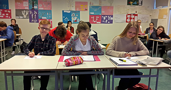 Finnbogi Örn in his classroom, sitting at his desk with his classmates around