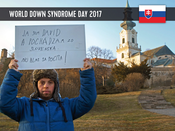 A male youth with Down Syndrome showing a sign with his statement
