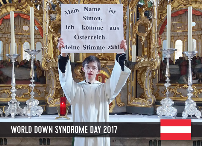 Young man with Down syndrome in a church, holding up a board with his statement.