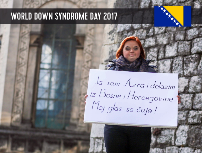 Young lady with Down syndrome standing in front of a church and holding up a poster with a statement.