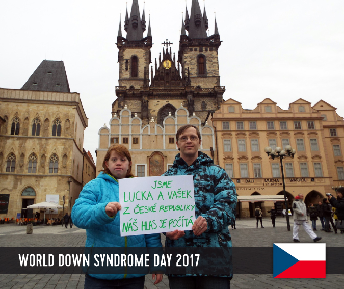 Young couple with Down syndrome on the old town square in Prague holding up a sign with their statement.