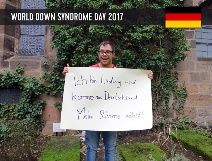 Young male from Germany with Down syndrome holding up a sign with his statement.