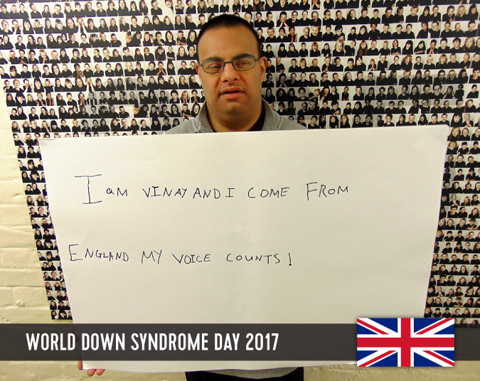 Young man with Down syndrome holding a sign in front of him with his statement to WDSD 2017.