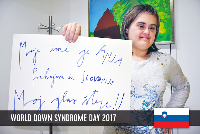 Young women with Down syndrome holding a sign with her statement