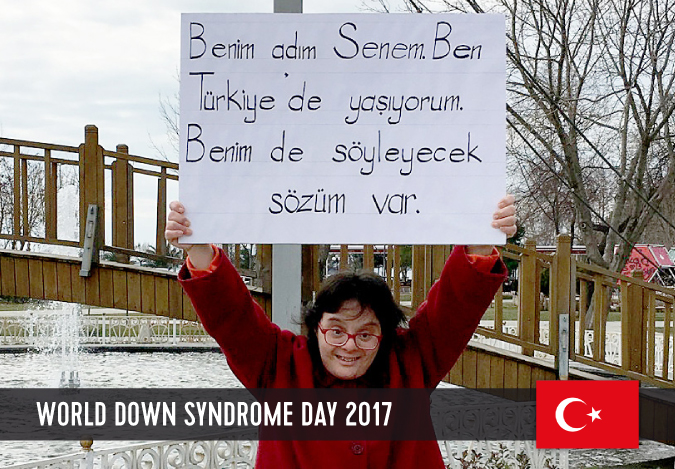 Young woman with Down syndrome holding a sign above her head with her statement to WDSD 2017.