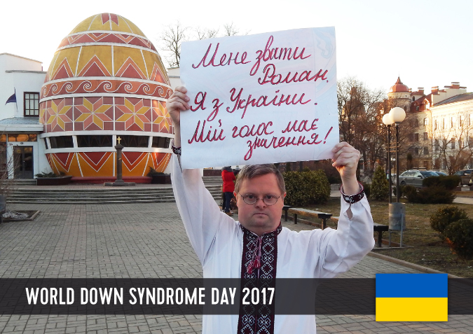 Young man with Down syndrome holding a sign above his head with his statement to WDSD 2017.