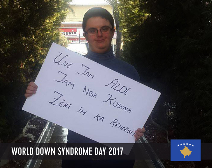 Young male person with Down syndrome holding a sign with his statement in front of his chest.