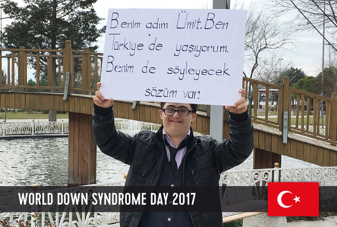 Young man with DS from Turkey holding a sign with his statement on WDSD 2017 above his head.