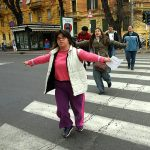 Young women with Down syndrome on a pedestrian crosswalk, spreading her arms