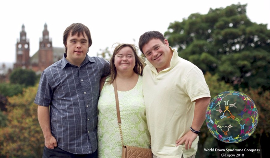 Three young people with Down syndrome, standing in front of some trees. with a church in the background.