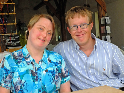 Young woman and young man with Down syndrome smiling at the camera.