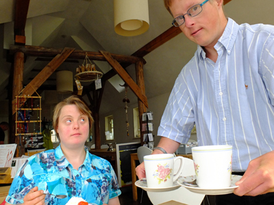 A waiter with Down syndrome is serving coffee to a young women with Down syndrome