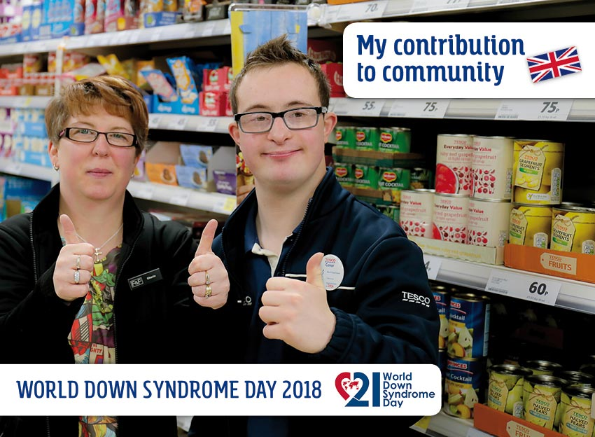 Conor (with DS) and his colleague stand in front of a food shelf in the supermarket. They look at the camera and show the gesture thumbs up.