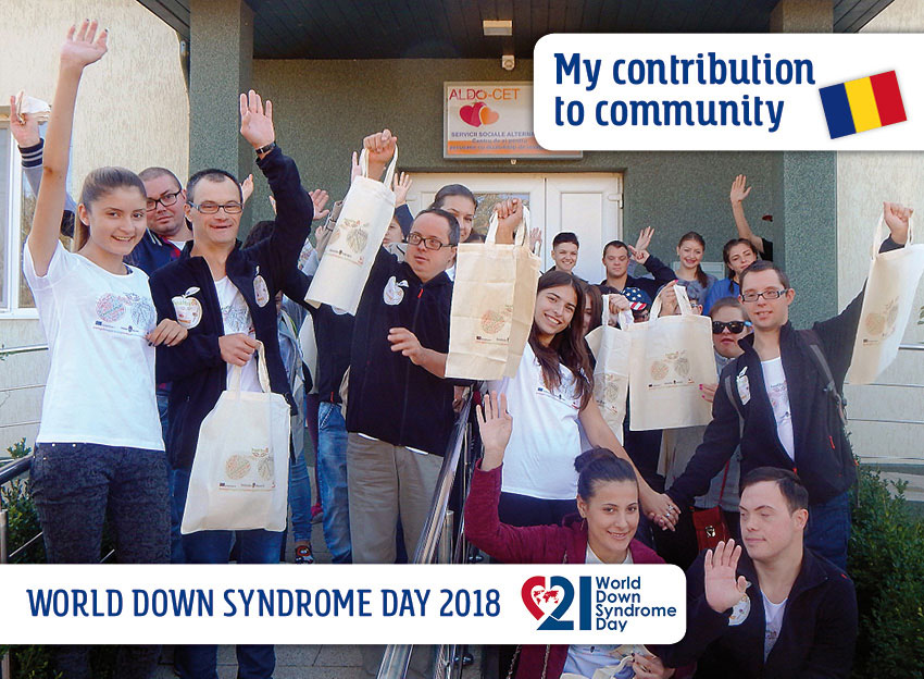 The group of volunteers - young women and men with and without Down syndrome - in front of the entrance to their club house. They wave, some with a textile bag advertising an educational program, in their hands.