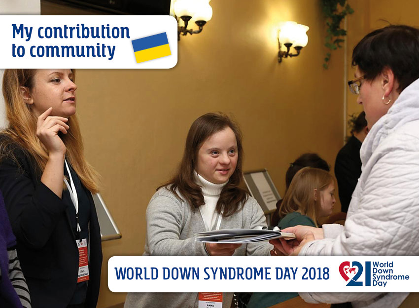 A young woman with DS at the reception desk greets a participant of the congress and presents her information material about the event.