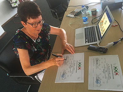Cora Halder signing certificates of participation