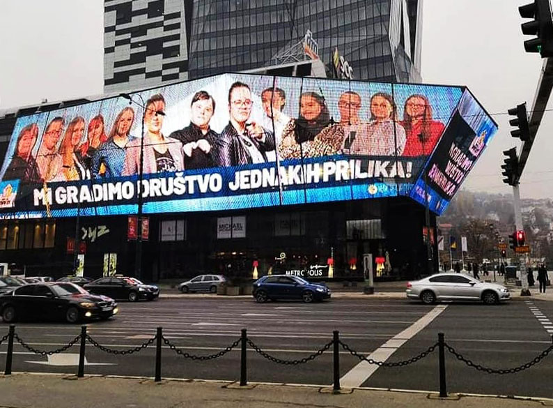 Big banner with a (fictitious) election advertisement featuring candidates with Down's syndrome as an eye-catcher on a commercial building. The Motto is: We build a society of equal opportunities!
