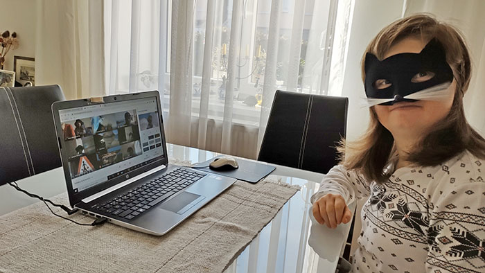 Young woman wearing a cat mask chatting with friends via video at her laptop