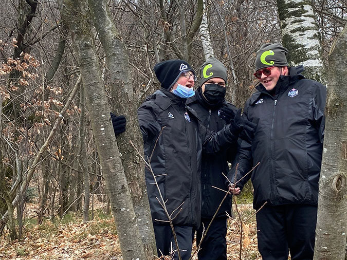 Three members of the Chameleon football team in the forest
