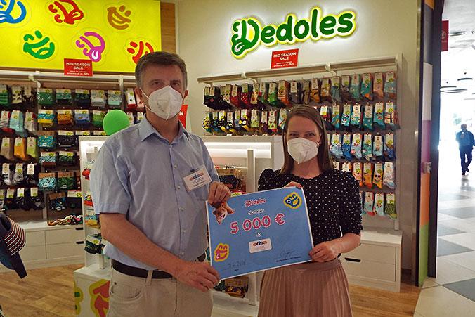 Isidro Moyano, the treasurer of EDSA with Kristína Vísková in the Dedoles Shop in Prague. Ms. Vísková is handing over the donation voucher for EDSA.